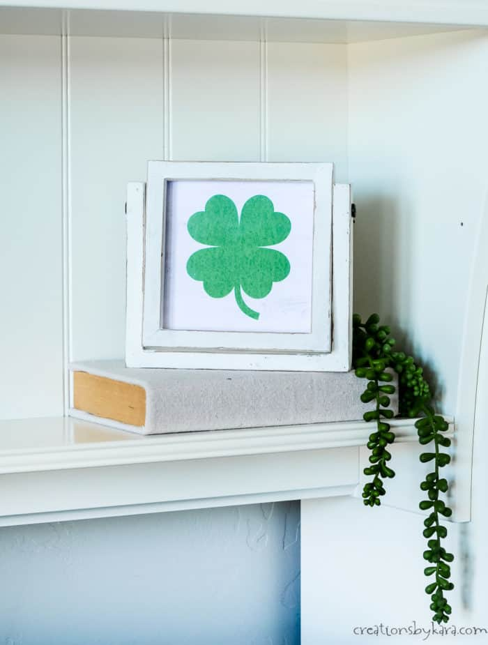 framed shamrock printable on a stack of books on a shelf
