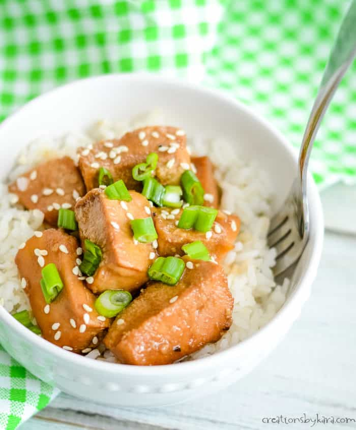 bowl of rice and chicken with homemade teriyaki sauce, sesame seeds, and green onions