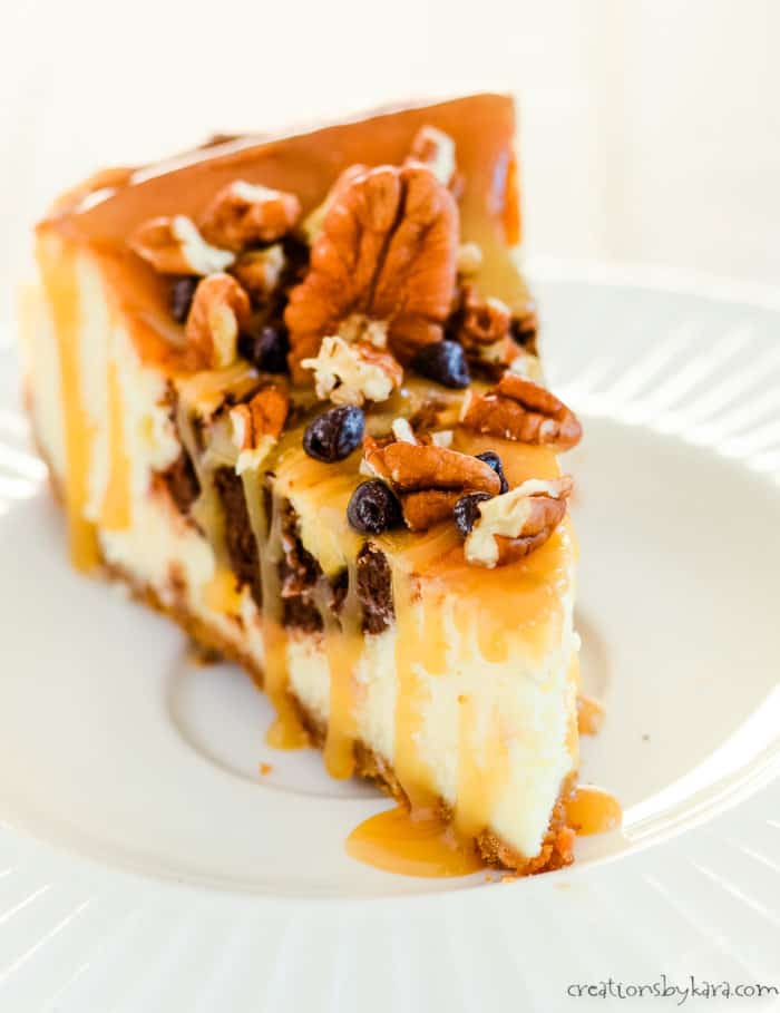 slice of turtle cheesecake on a plate with pecans, chocolate chips, and caramel sauce on top