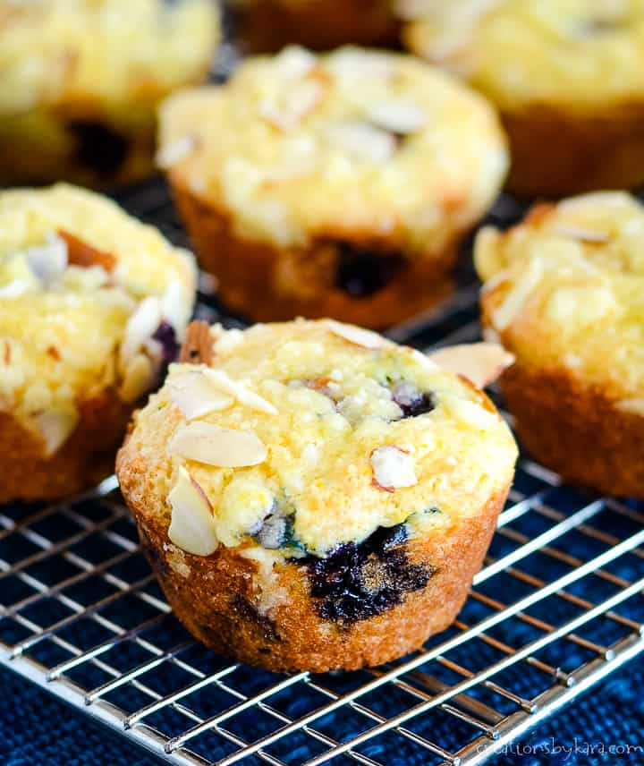 blueberry orange muffins topped with almond crumb topping on a cooling rack