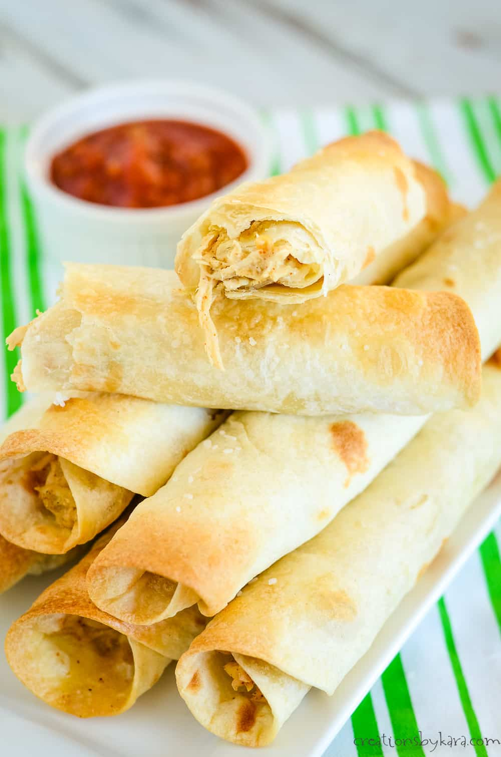 chicken and cheese flautas on a tray with salsa