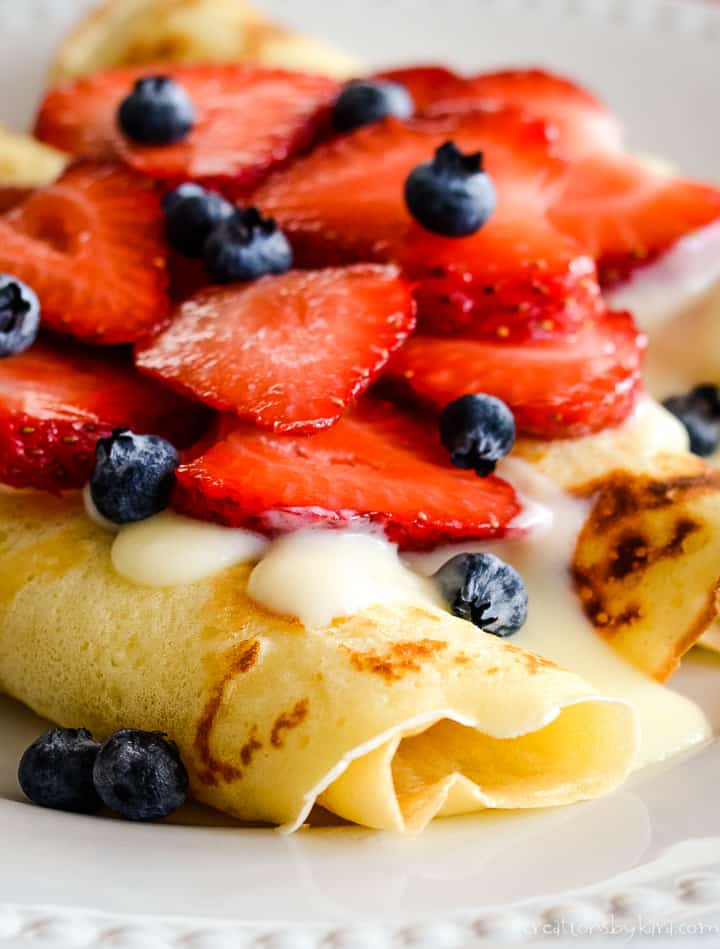 rolled thin pancakes with vanilla sauce and berries