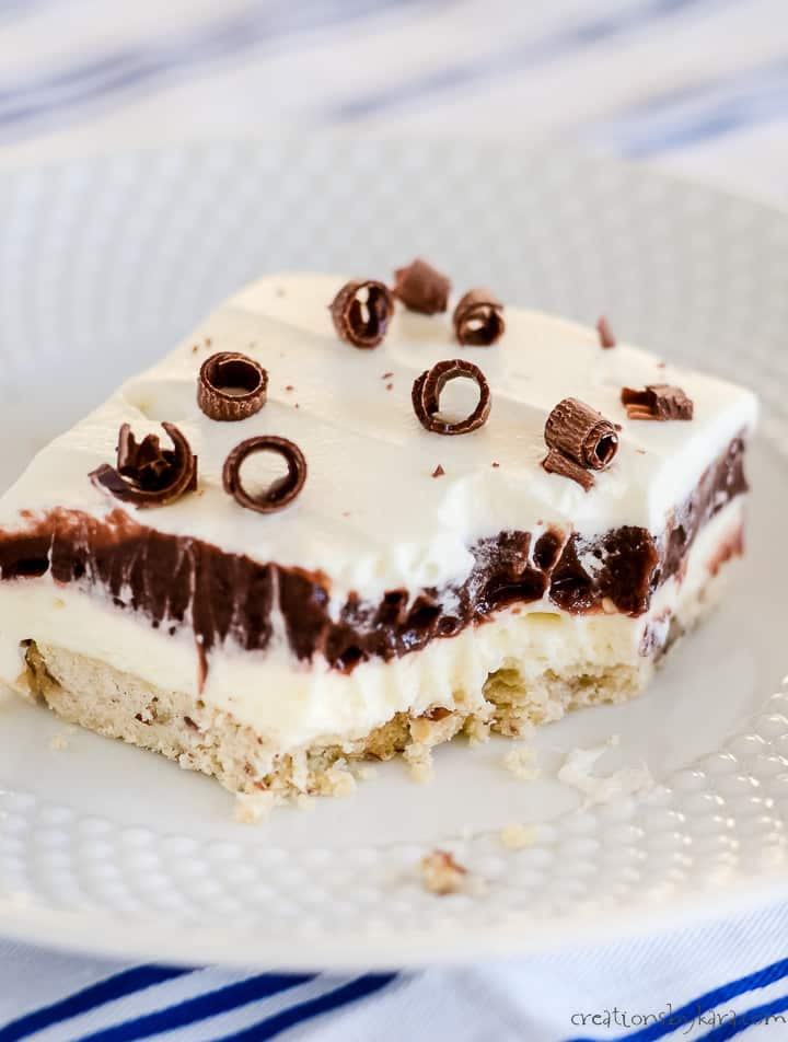 chocolate layer dessert on a white plate with a bite taken out of it
