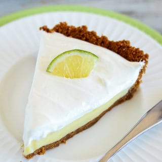 slice of key lime pie on a plate garnished with a lime wedge