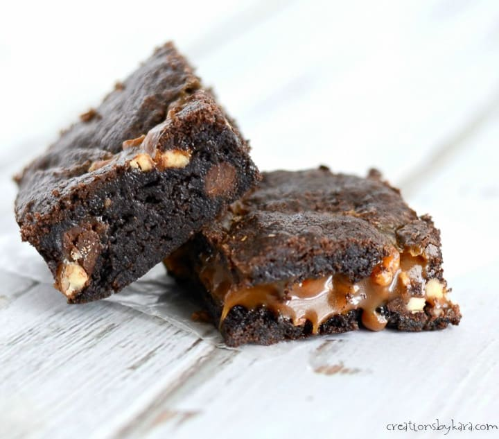 two warm caramel turtle brownies with caramel oozing out