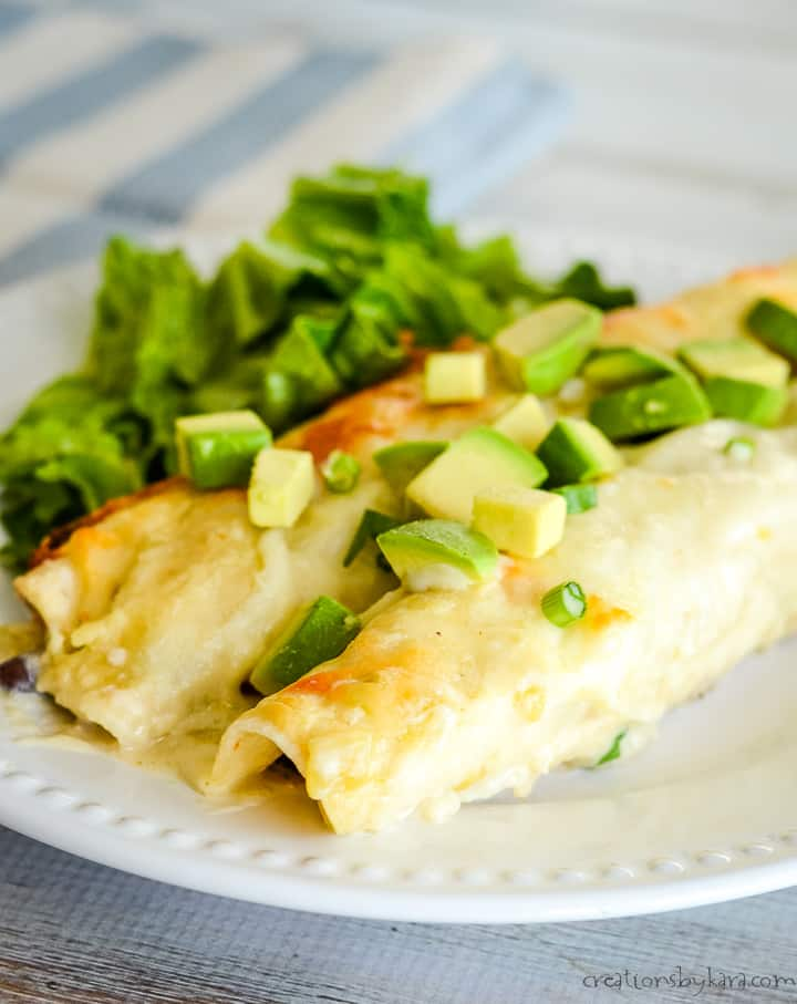 two shredded chicken enchiladas on a plate with avocados and lettuce