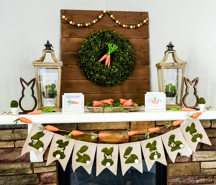 close up of easter mantel with banner, wreath, lanterns, and carrots