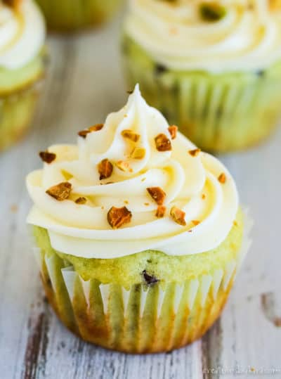 pistachio cupcake topped with cream cheese frosting and chopped pistachios