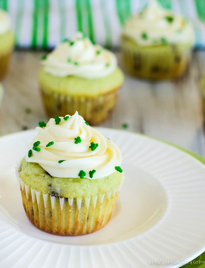 pistachio cupcake on a plate with green sprinkles
