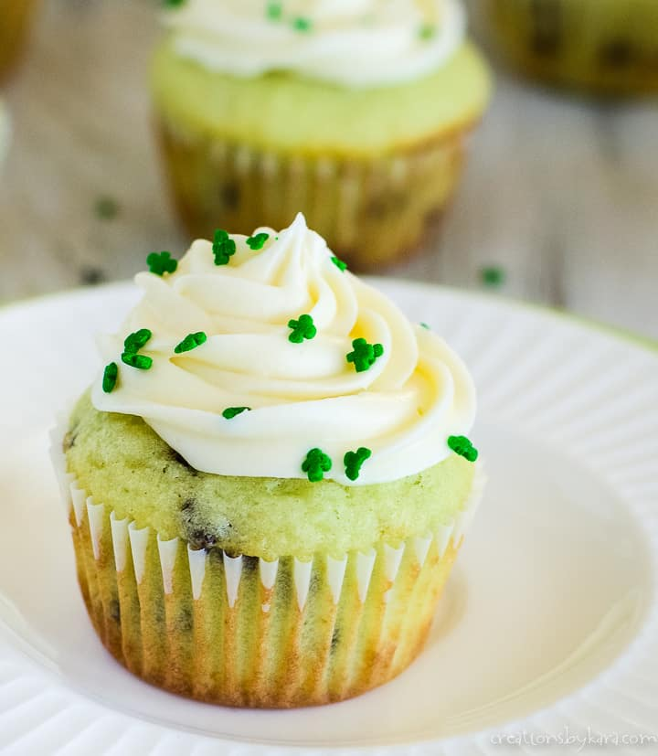 close up of pistachio pudding cupcake topped with frosting and shamrock sprinkles