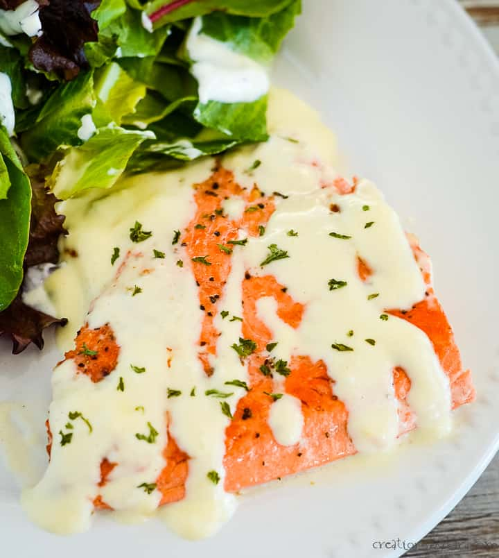 overhead shot of salmon topped with cream sauce and parsley