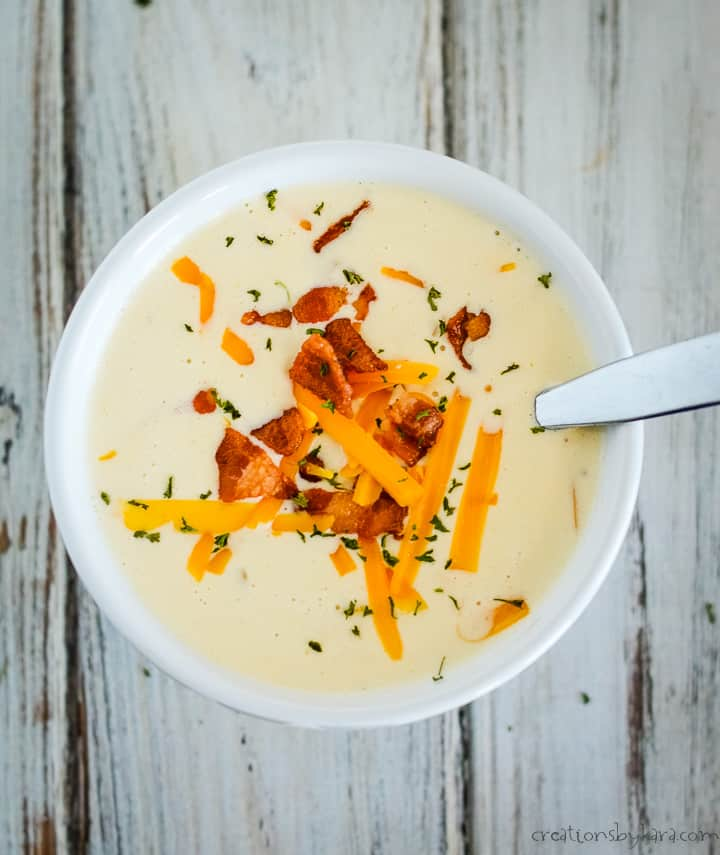 overhead shot of cream of cauliflower soup garnished with bacon, cheddar, and parsley