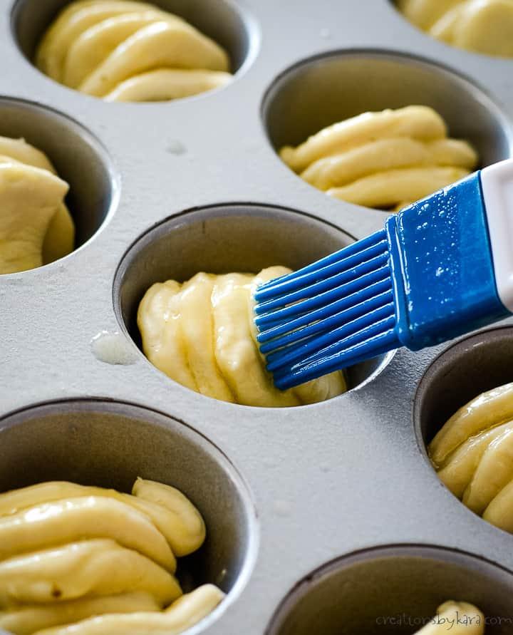brushing garlic butter on garlic roll dough before baking