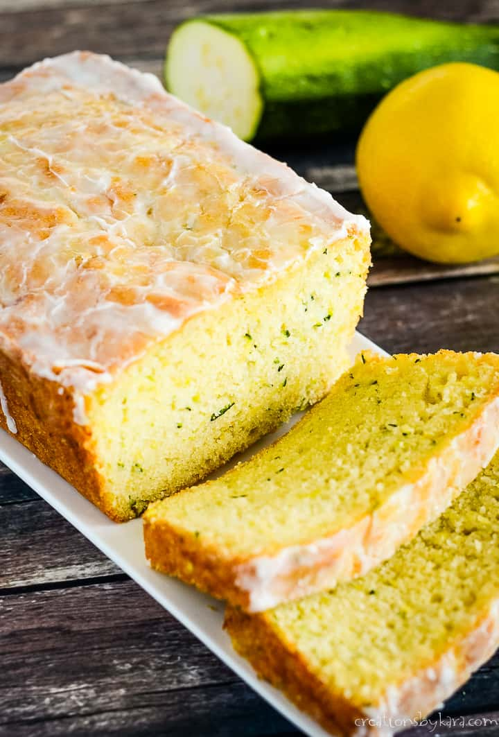 glazed lemon zucchini bread with lemon and zucchini in the background
