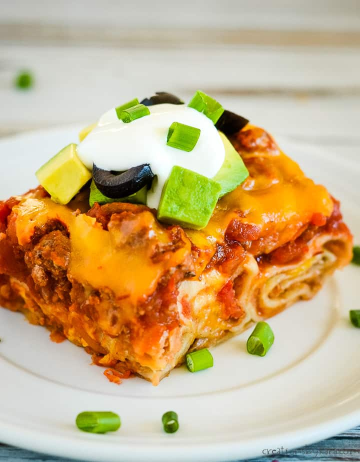 mexican lasagna with flour tortillas on a plate with sour cream, olives, avocados, and green onions