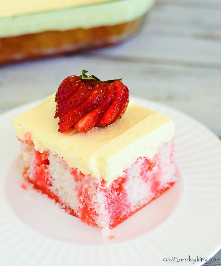 sliced strawberries on top of strawberry jello poke cake