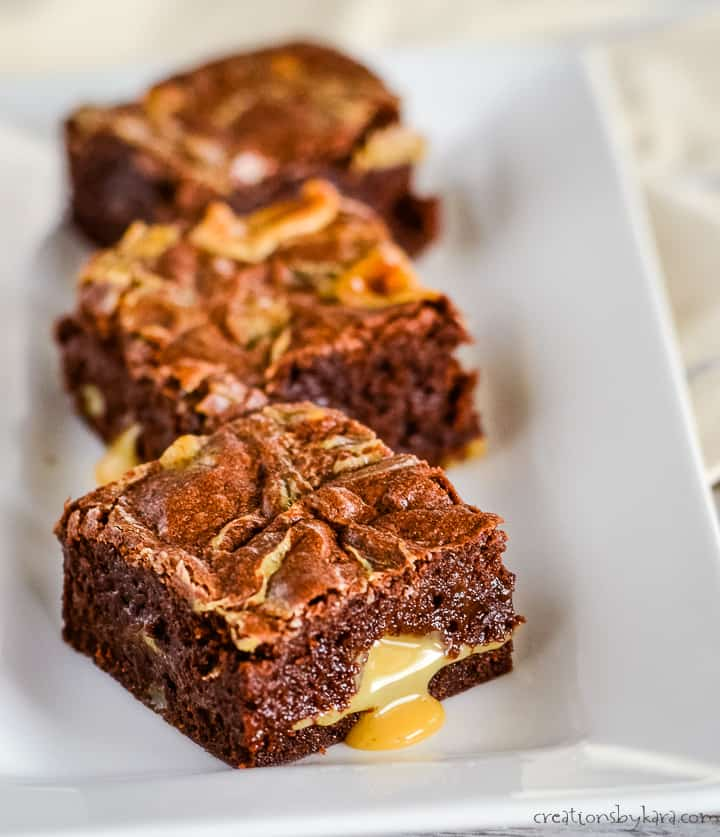 brownies on a tray with caramel dripping down the side of the brownie