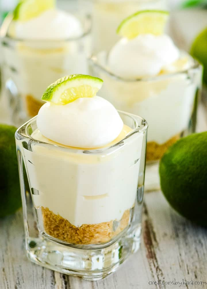 mini no bake lime cheesecakes with whipped cream and a slice of lime