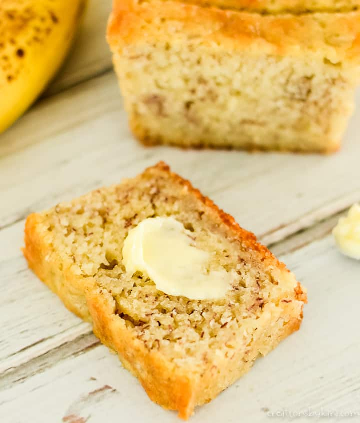 slice of buttered banana bread with a loaf in the background