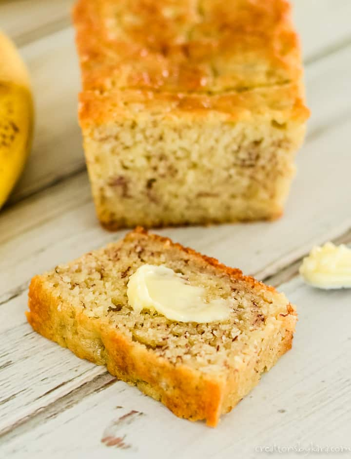 slice of super moist banana bread spread with butter