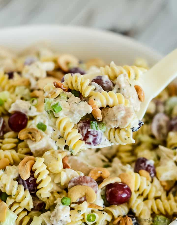 cold chicken pasta salad being scooped from a bowl