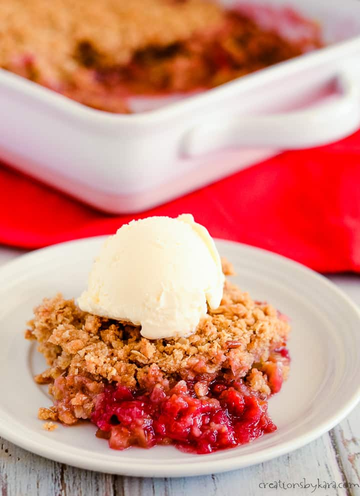 plate of rhubarb crisp with a pan of crisp in the background