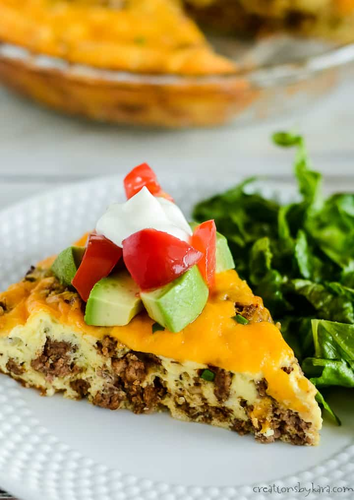crustless taco pie on a plate with lettuce, topped with sour cream, tomatoes, and avocados