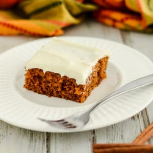 pumpkin bar with cream cheese frosting on a plate with a fork